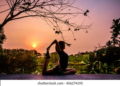 Silhouette Asian girl practicing yoga in a park at sunset. The pose called One-Legged King Pigeon, Eka Pada Rajakapotasana. Only the model is in focus while the background is blur due to DOF technique