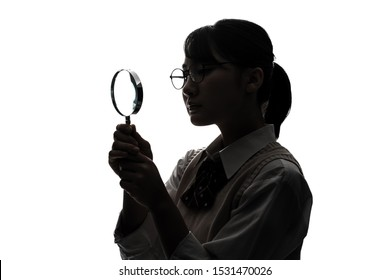 Silhouette of asian high school girl holding a loupe.
