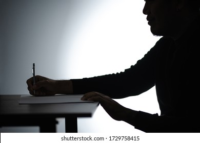 Silhouette asian man writing on table. Beared man writing on Notebook. Freelancer man Blogger writing at Home on desk.