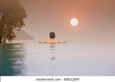 Silhouette of asian person  at the edge of infinity swimming pool,looking at the Ocean sunset