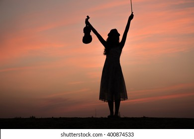 silhouette of asian woman play violin on sunset