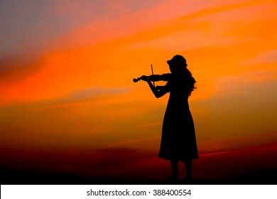 The silhouette of asian woman playing violin over beautiful twilight sunset.