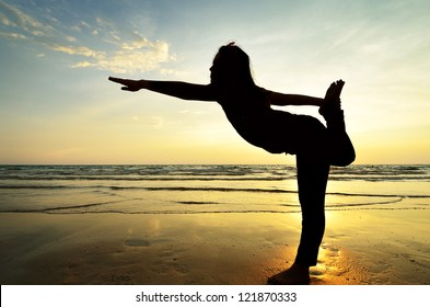 silhouette Asian woman practicing yoga at the beach