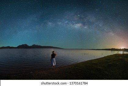 The Silhouette of an Asian woman standing alone with loneliness, sadness, disappointment from love. Outdoor lakeside on the night of the stars and the Milky Way. Long Exposure, with grain.