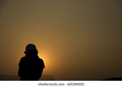 Silhouette of a Asian woman standing around the mountain on sunset