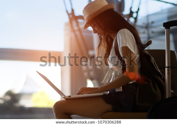Silhouette of asian woman teenager using laptop computer at airport terminal sitting with luggage suitcase and backpack for travel in summer relaxing waiting flight transport