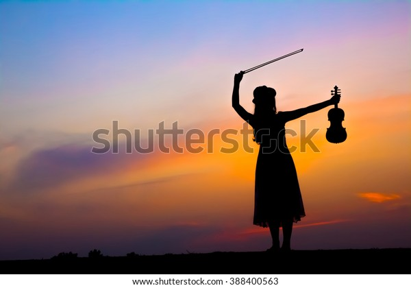 The silhouette of asian woman with the violin over beautiful twilight sunset.