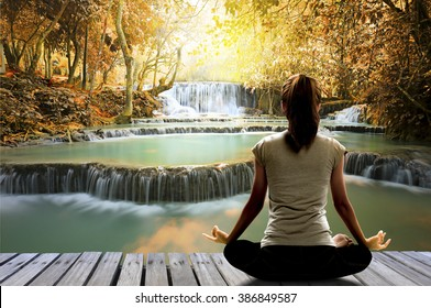 Silhouette of Asian woman yoga on the wooden bridge over waterfall in the autumn forest at the sunrise in the morning. Image create for business, healthcare, sport and lifestyle of people.,
