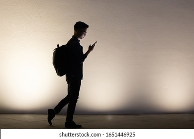 silhouette of asian young man use smart phone outdoor in the evening