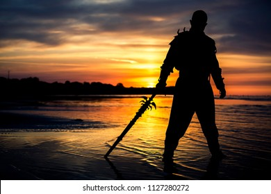 Silhouette of assassin with the sword at the beach. He is posing at the sea during beautiful, orange, yellow sunset.