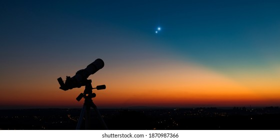 Silhouette of a astronomy telescope with twilight sky.