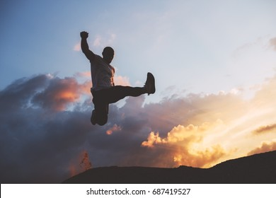 Silhouette of an athlete jumping against background of beautiful clouds at sunset. Athlete jumps. Parkour, freerun. Intentional dark colors