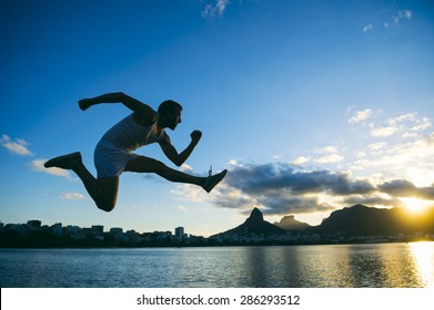 Silhouette of athlete jumping in front of the sunset skyline at Lagoa lagoon in Rio de Janeiro, Brazil
