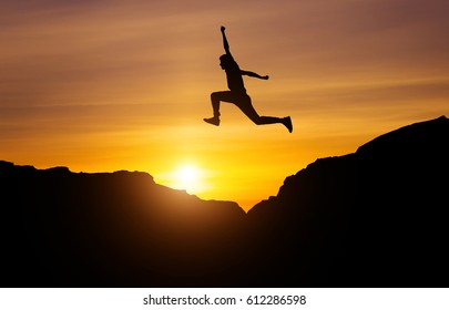 Silhouette of athlete, jumping over rocks in mountain area at sunset