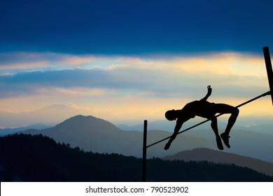 Silhouette of athlete jumping pole vault with mountains in the background