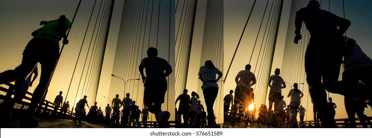 Silhouette of athletes running marathon with strong back light at summer sunrise