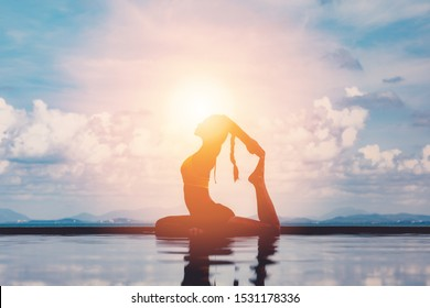 silhouette Athletic Asian woman relaxing in yoga king pigeon pose on the pool above the beach with beautiful sea in Tropical island,Feeling comfortable and relax in holiday,Vacations Concept