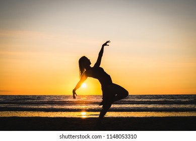 Silhouette of an athletic dancer stretching on the beach at the sunset. Beautiful golden colors