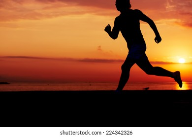 Silhouette of athletic runner jogging on the beach against orange sunrise, male jogger with muscular body in action, sportsman running with the speed, fitness and healthy lifestyle concept