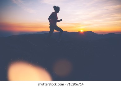 Silhouette of athletic woman finishes workout in the mountains at sunset. Sport tight clothes. Intentional motion blur.