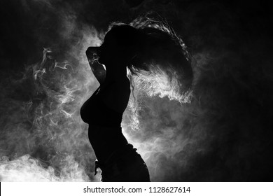 Silhouette of Attractive Body Shape Fluttering Curl Hair in Smoke Fog with back light Black Background, Concept of Sport sexy girl focus attention on exercise dance fit firm loss weight, motion blur