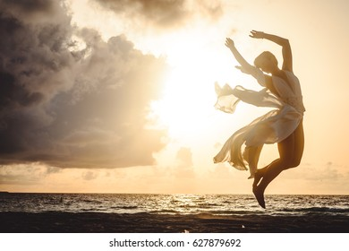 silhouette of an attractive and sensual young woman, dancing at the sunset on a solitary beach