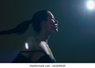 Silhouette of attractive sexy woman under light over dark background