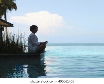 Silhouette of attractive woman sitting in meditating position by the pool