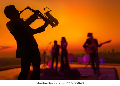 Silhouette autumn or winter scene of saxophone musician man showing with blurry jazz trio band and twilight or sunset cityscape background. Image for happy new year party or celebration concept.