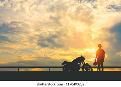 Silhouette of Back biker or rider,motorbike parking with sunset background .Traveller man standing and holding helmet beside motorcycle.Trip and lifestyle of motorbike concept,copy space.