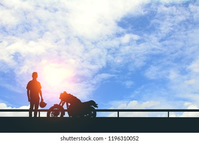 Silhouette of Back biker or rider,motorbike parking with blue sky background .Traveler man standing and holding helmet beside motorcycle.Trip and lifestyle of motorbike concept,copy space.