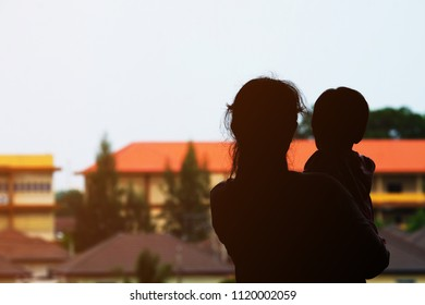 Silhouette of back side of woman holding baby with the burry background of buildings