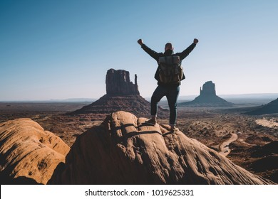 Silhouette back view of excited male traveler raising hands up standing on rock over desert with monuments in Navajo reservation, hipster guy happy about reaching destination exploring USA landmarks