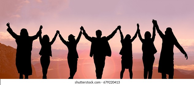 Silhouette back view of group international business people united hands and raised hands up together with spirit teamwork on the top of mountain, success teamwork concepts or collaboration concepts