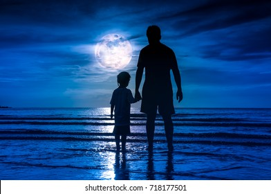 Silhouette back view of loving child holding hands her father, standing in the sea. Family enjoying and relaxing on beach with full moon on blue sky background. The moon taken with my own camera.