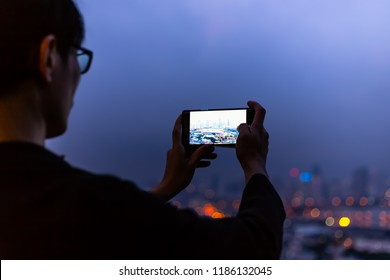 silhouette of Back view young man takes pictures by cellphone on the rooftop bar in the cityscape with bokeh background