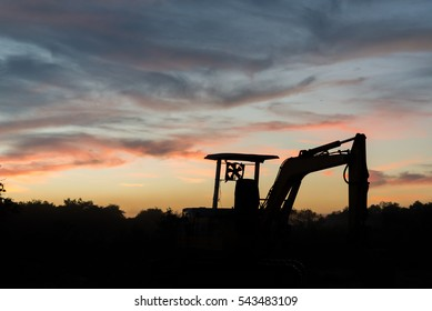 silhouette of Backhoe loader stone , with sunset view.