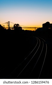 Silhouette of a backlit 25 April Bridge in Lisbon, Portugal at sunset with train tracks on foreground