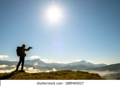 Silhouette of a backpacker photographer taking pictures of morning landscape in autumn mountains with digital camera.
