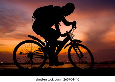 Silhouette of backpacker ride mountain bike on bridge beside sea with sunset sky background