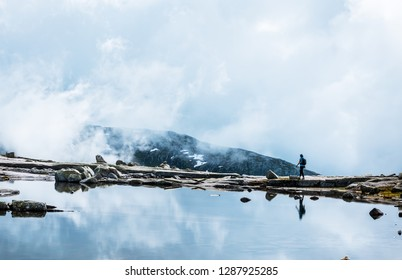 Silhouette of backpacker walking towards the edge of rocky lake. near Trolltunga, Norway