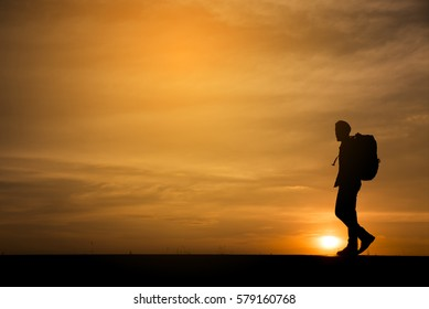 Silhouette of backpacker,person side view walking toward successful.Asian lonely man with sunset background in Thailand.Travel and success concept