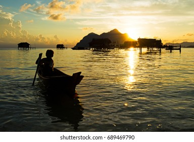 Silhouette of bajau laut young boy paddling a boat during sunrise at the shore of Maiga Island in the vicinity of Sipidan Island and Tun Sakaran Marine Park, Semporna, Sabah Borneo, Malaysia.