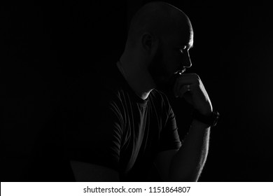 Silhouette of a bald man on a black background