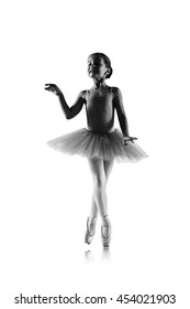 silhouette of ballet dancer girl in pointe and tutu isolated on white, little ballerina with working foot pointing front in second position. Education lessons in Classic dance school black and white