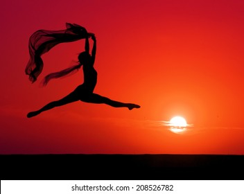 Silhouette of a ballet dancer leaping in front of a red sunset