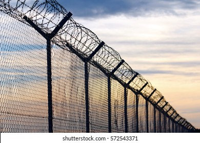 Silhouette of Barbed Wire fence against a Cloudy Sky