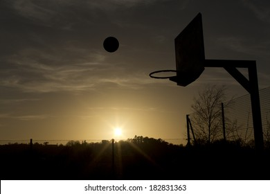 Silhouette of a basketball in mid air over the sunset about to score. Concept of sport, with copy space and sun flare