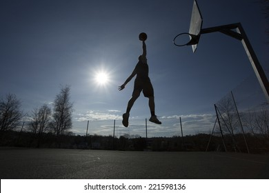 Silhouette of a basketball player in mid air on an outdoor basketball court about to slam dunk on a bright sunny day, motion blur