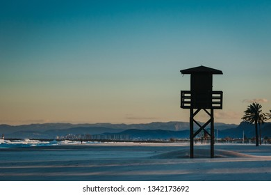 Silhouette of baywatch tower in famous Spain holiday destination beach. Mountains and city in the background with warm sunset light.